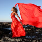 artistic image of ebony model against a blue sky by the seaside. she is holding up a red cloth and is dressed in a regal red dress