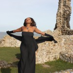 ebony model just eden uk arching towards the sun against a background of ruins