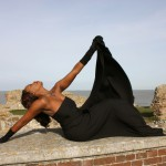 ebony artistic model just eden uk stretching out and soaking up the sun wearing a black dress and black gloves
