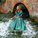 ebony artistic model just eden uk sitting under a bridge wearing a green evening dress